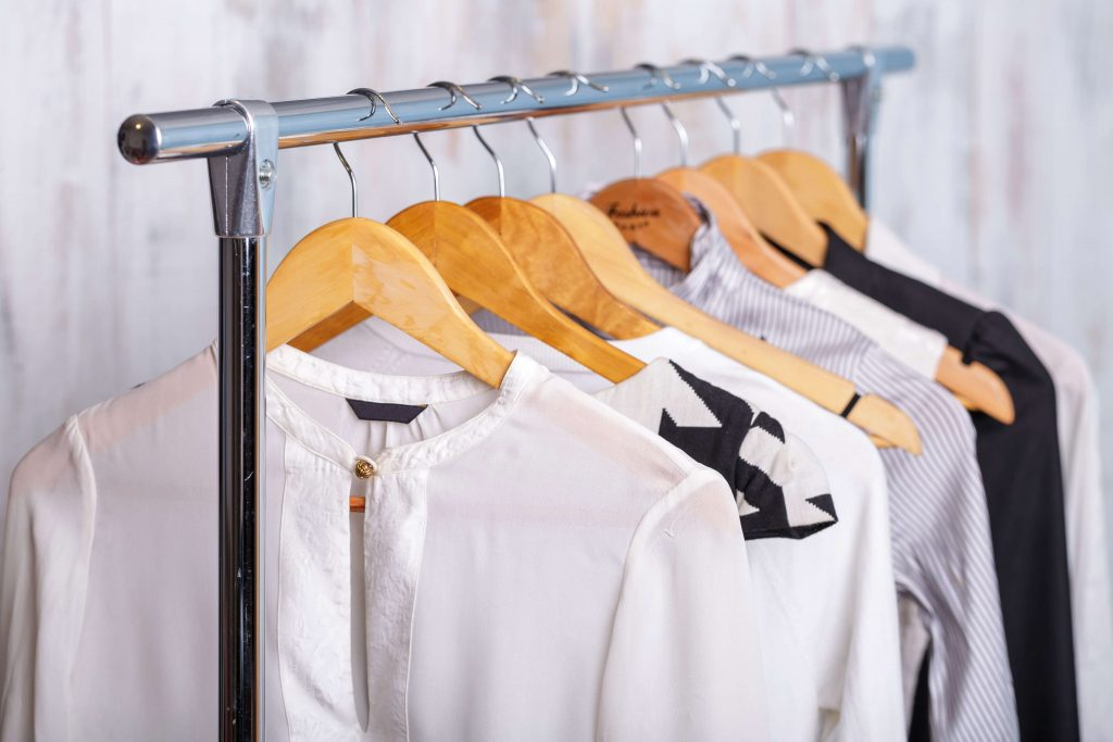 Drycleaned clothes hanging up on rack.